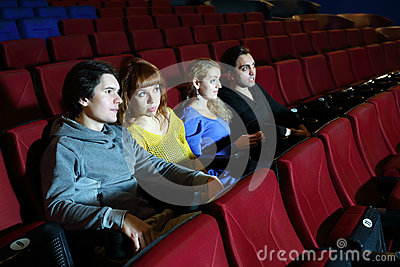 Two happy couples look movie and talk in cinema theater