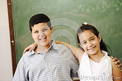 Two happy friends in front of green classroom boar