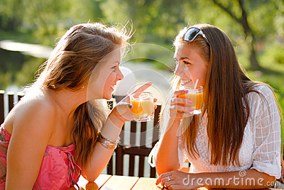 Two happy girl friends in terrace cafe & chatting