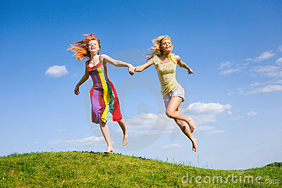 Two happy girls fleeing on a meadow.