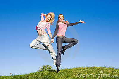 Two happy girls jumping on green meadow