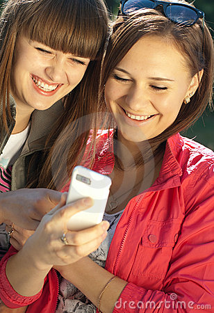 Two happy girls with mobile phone