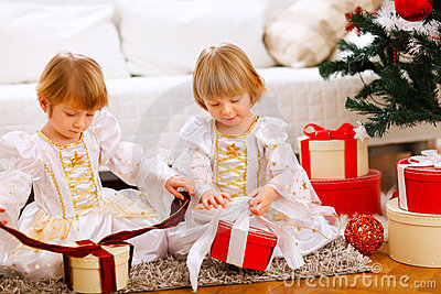 Two happy girls opening gifts near Christmas tree