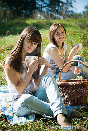 Two happy girls on picnic drinking tea