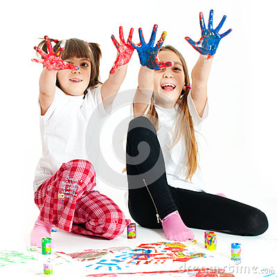 Two happy girls playing with finger colours