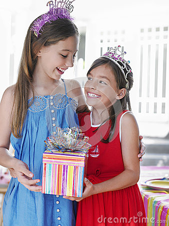 Two Happy Girls In Tiaras Holding Present