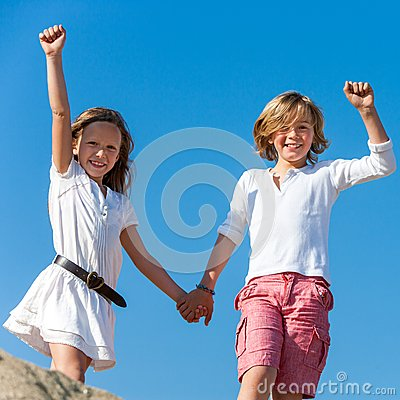 Two happy kids raising hands outdoors.