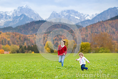 Two happy laughing kids in field between mountains