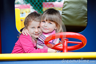Two happy little girls embracing on playgroung