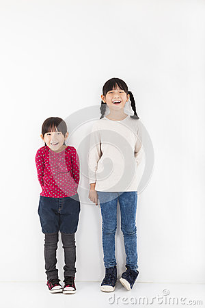 Two happy little girls stand before white wall