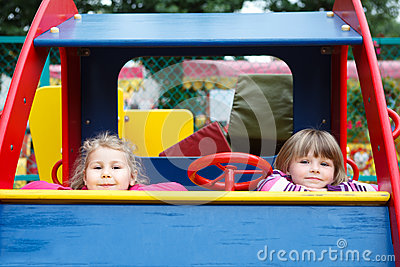 Two happy playful girls sitting in car toy