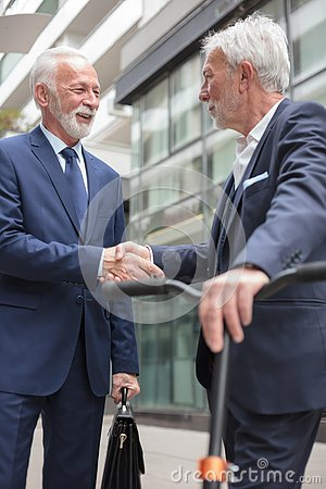 Free Two Happy Senior Businessmen Shaking Hands, Standing In Front Of An Office Building Royalty Free Stock Image - 142619806
