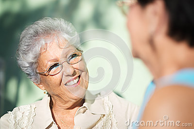 Two happy senior women talking in park