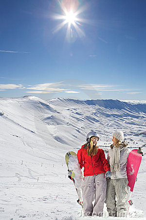 Two happy snowboarders in snow covered mountains