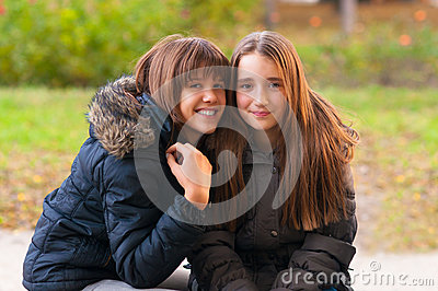 Two happy teenage girls having fun in the park