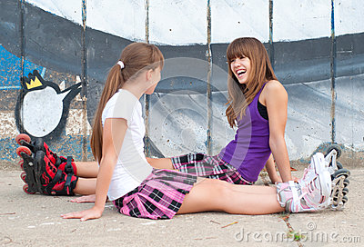Two happy teenage girls in roller skates