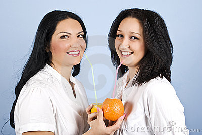 Two happy woman drink orange juice