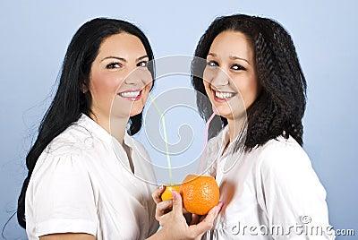 Two happy woman drink orange juice