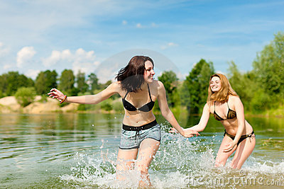 Two happy women having fun at lake in summer