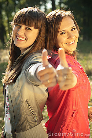 Two happy women with thumbs up