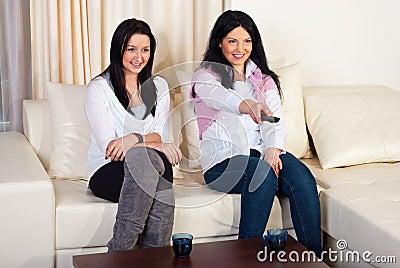 Two happy women watching tv