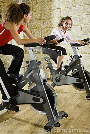 Two happy women working out on exercise bikes