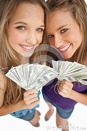 Two happy young beauty holding dollars
