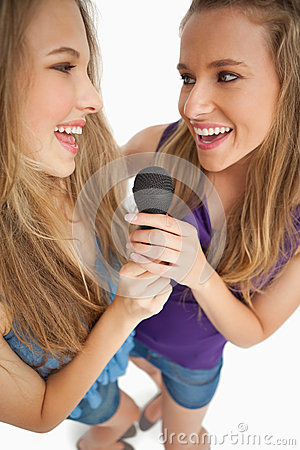 Two happy young beauty singing together