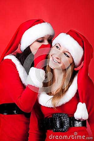 Two happy young Santa girl talking