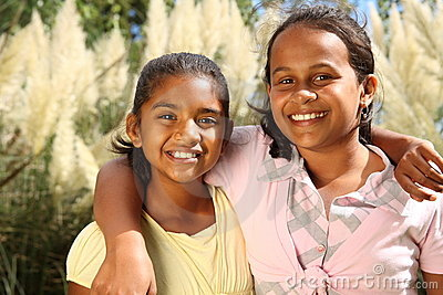 Two happy young school girls in friendship hug