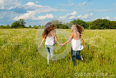 Two happy young women running on green field