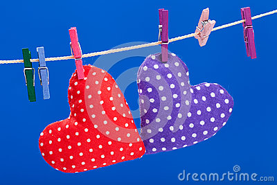 Two hearts hanging on a clothesline with clothespins