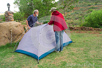 Two hikers assemble tents on camping site