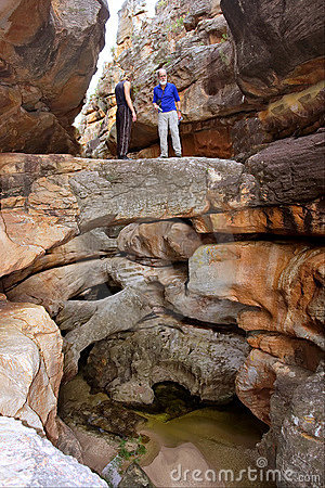 Two hikers stand on natural bridge