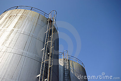 Two huge industrial silos against a blue sky