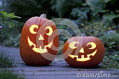 Two Illuminated Halloween pumkins in the garden