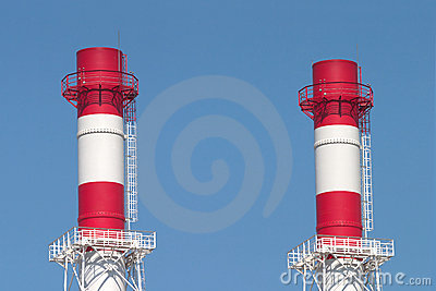 Two industrial smoke pipes over blue sky