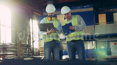 Two inspectors are having a discussion in a factory unit professional heavy industry engineers. Two inspectors are having a discussion in a factory unit. 4K stock footage