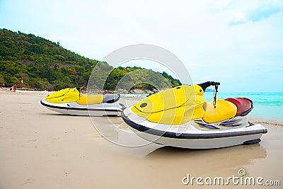 Two jetskis on sandy beach