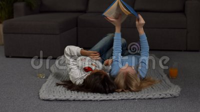 Playful children reading a book on the floor stock footage