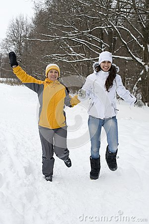 Two joyful women in winter jackets and caps run on