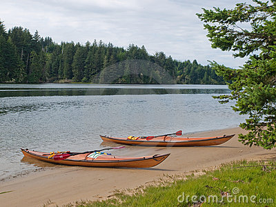 Two kayaks on beach with trees along slough