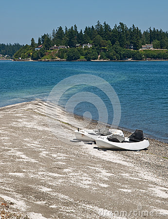 Two kayaks on sand spit with houses on shore