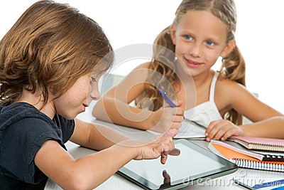 Two kids doing homework on digital tablet.