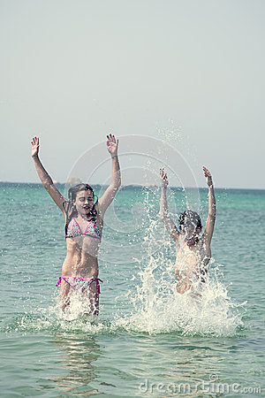 Two kids jumping and playing in the ocean