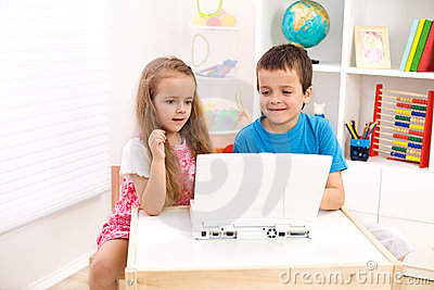 Two kids looking at laptop computer