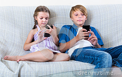Two kids looking to smartphones on sofa Stock Photo
