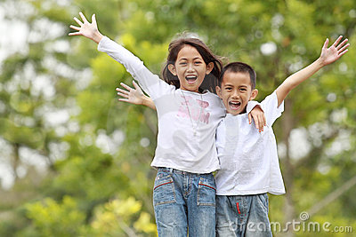 Two kids outdoor raise their hand and smile