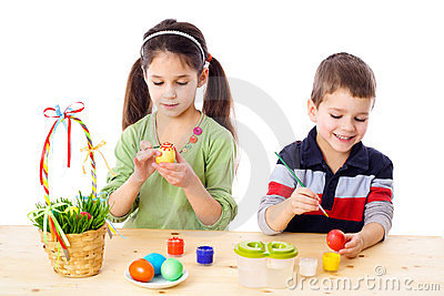 Two kids painting easter eggs