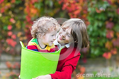 Two kids playing in garden with laundry basket